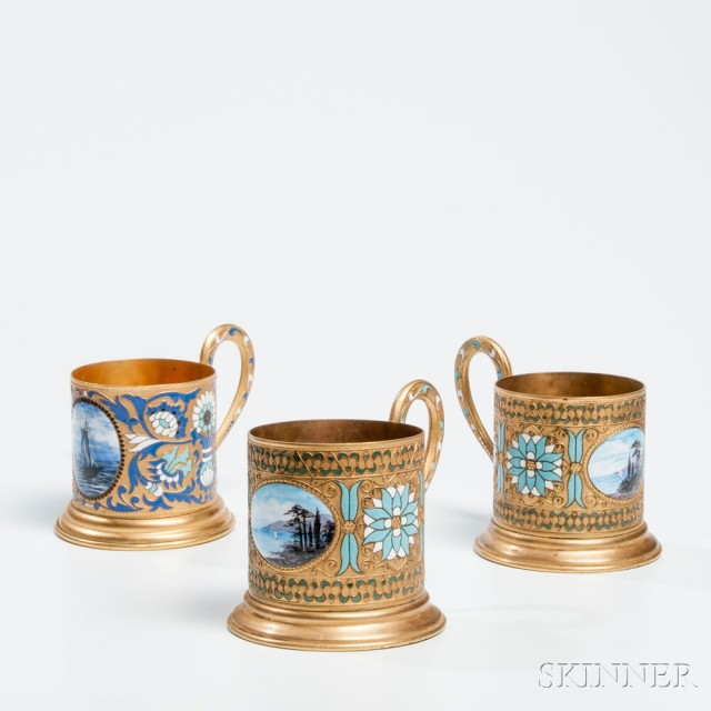 Three Russian Enameled Brass Cups with Scenic Medallions, 20th century (Estimate:   $300-500)